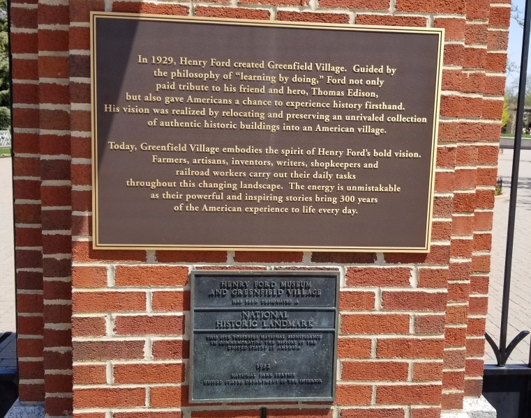 """The two plaques at the entrance to Greenfield. The top one reads, """"In 1929, Henry Ford created Greenfield Village. Guided by the philosophy of 'learning by doing,' Ford not only paid tribute to his friend and hero, Thomas Edison, but also gave Americans a chance to experience history firsthand. His vision was realized by relocating and preserving an unrivaled collection of authentic historic buildings into an American village. """"Today, Greenfield Village embodies the spirit of Henry Ford's bold vision. Farmers, artisans, inventors, writers, shopkeepers and railroad workers carry our their daily tasks throughout this changing landscape. The energy is unmistakeable as their powerful and inspiring stories bring 300 years of the American experience to life every day."""" The second reads, """"Henry Ford Museum and Greenfield Village has been designated a National Historic Landmark. This site possesses national significance in commemorating the history of the United States of America. 1982. National Park Service. United States Department of the Interior."""""""