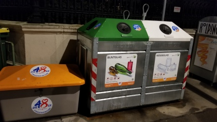 Just a few of the various outdoor recycling bin types, including multiple types of glass.