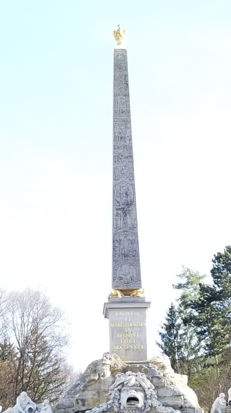 An egyptian-style obelisk in Schönbrunn. Hieroglyphics are visible along the structure.