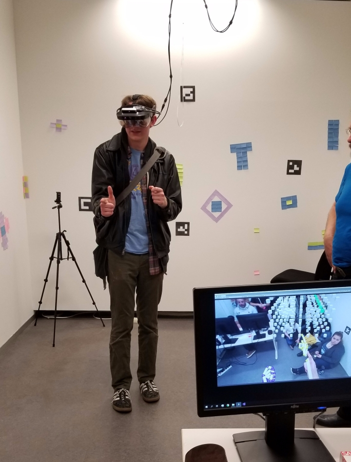 I try out a few hand gestures to select data in augmented reality. You can see my view in the bottom left.