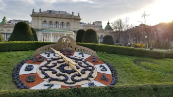 """The Kursalon music hall as viewed in Stadtpark. The clock in the hedge says """"Our Garden."""""""