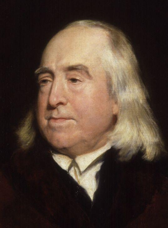 A painting of Jeremy Bentham, creator of the panopticon. Bentham is an older balding white man with an oval face, dark eyes, and white hair down to his shoulders.