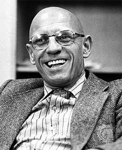 A black and white picture of Michel Foucault. Foucault is a bald man wearing glasses, a blazer, and a striped dress shirt. He is pictured laughing.