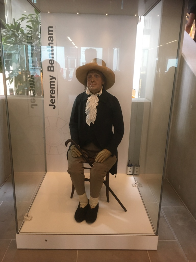 "Jeremy Bentham's ""Auto-Icon"" at The Student Centre in University College London. The Icon appears to be a model of a man wearing old fashioned clothes, including gloves and a hat. He is sitting on a wooden chair with a cane set between his legs. The model is inside a glass case."