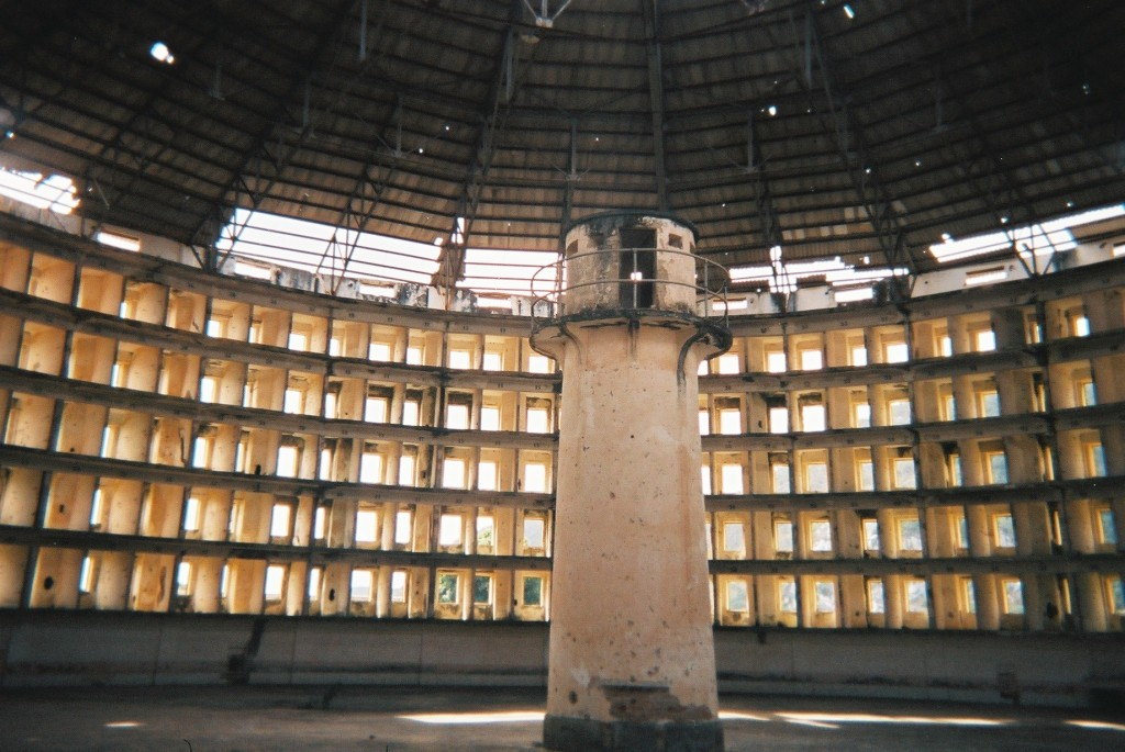 The Presidio Modelo in Cuba. The Presidio is a round building in a state of disrepair. The outer ring appears to consist of rectangular open windows, while a guard tower stands in the center.