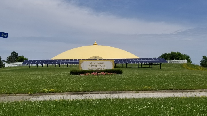 A large, low lying golden dome lies behind a row of solar panels. In the front, a sign reads Maharishi University of Management.