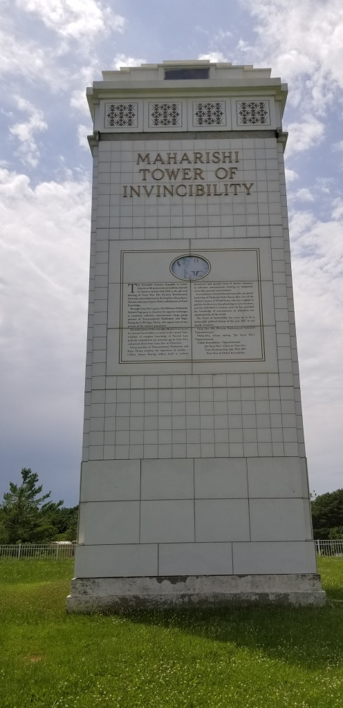 """A large white stone tower. Words near the top declare it the """"Maharishi Tower of Invincibility."""""""