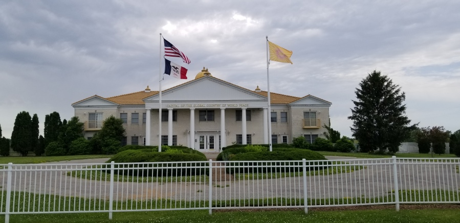 "A white and yellow building marked as the ""Capital of the Global Country of World Peace."" Two flagpoles out front display the American and Iowa flags (on the left), and the GCWP flag (on the right, a yellow flag with a pink sunburst design)."