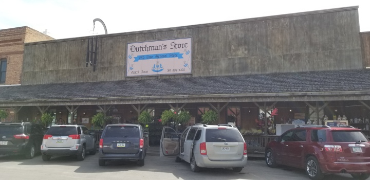"A large wooden store with an awning. A sign above the awning says ""Dutchman's Store: Old Time General Store."""