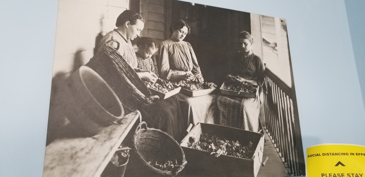 A black and white photo of three women and a young girl performing some sort of handiwork.