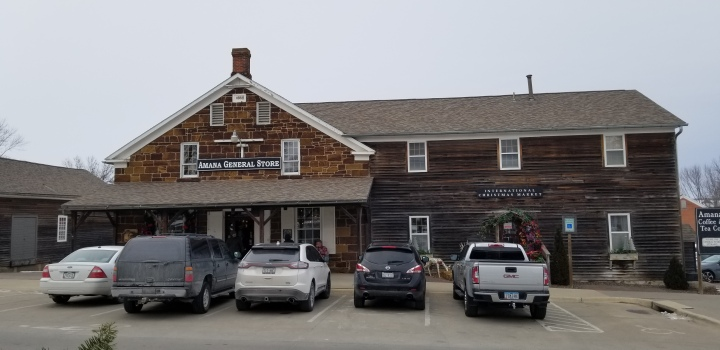 The Main Amana General store, a wooden building with several cars parked in front of it.