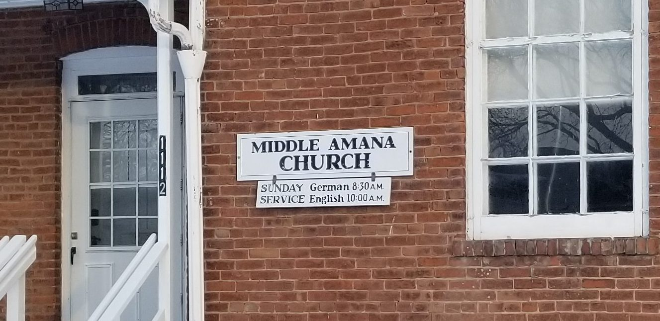 The entryway to the Middle Amana Church, including the service schedule with both German and English services.