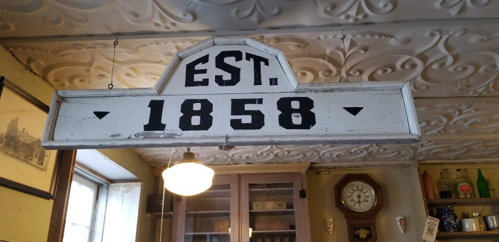 A wooden sign saying Est. 1858 hanging from a metal ceiling with a floral design.