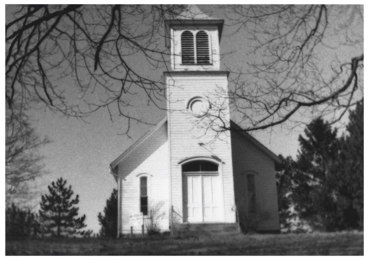 A black and white photo of a church. The church has white siding and a modest steeple.